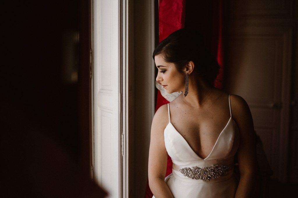 Photographe Mariage Le Mans mariée devant fenetre dans chambre chateau