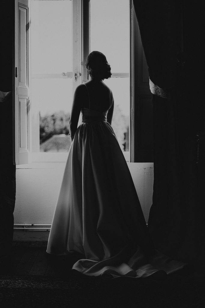 Mariage au Château de Chéronne mariée devant fenetre dans chateau en noir et blanc