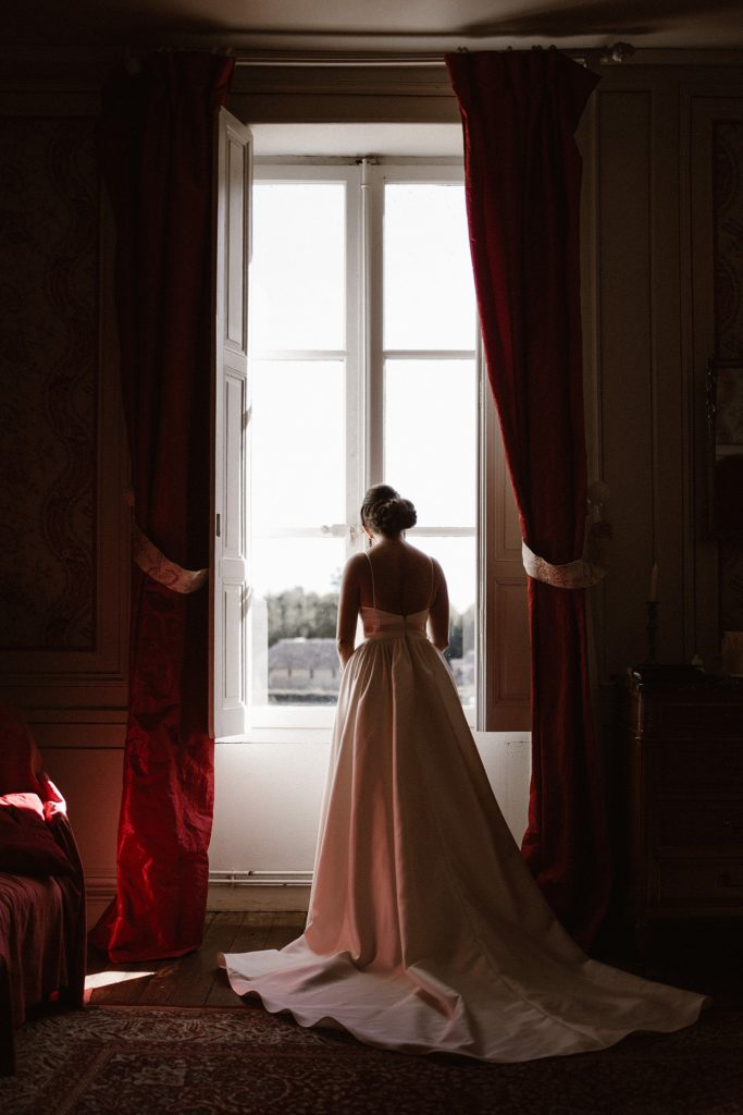 Photographe Mariage Le Mans photo de la mariée devant la fenetre de la chambre