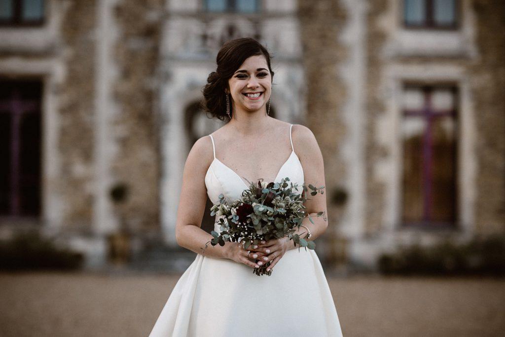 Mariage au Château de Chéronne mariée avec bouquet devant chateau
