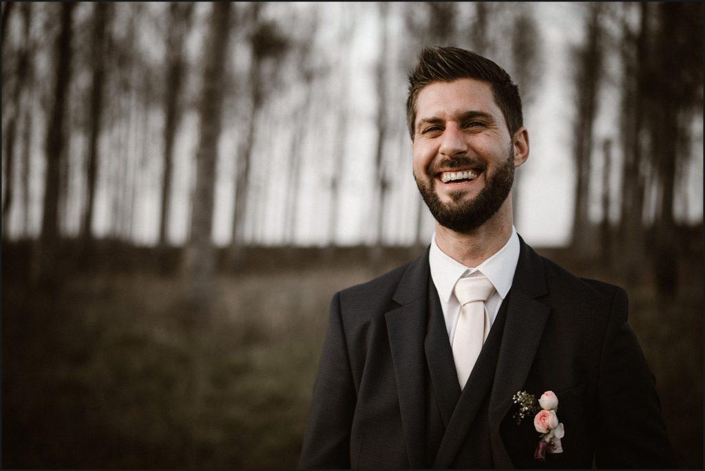 Mariage à la Ferme du Grand Hôtel du Bois marié souriant pendant photo de couple dans les bois