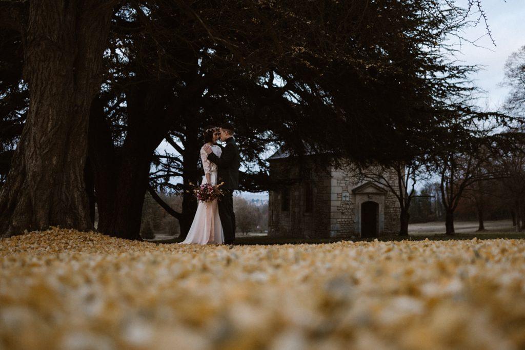 Mariage Moody photo de couple en hiver sur tapis de feuilles jaune