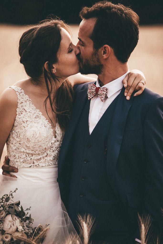 Photographe Mariage Bretagne baiser des mariés dans champ de blé