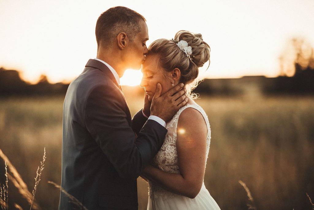 Photographe Mariage Prieuré de Vernelle marié embrasse le front de la mariée
