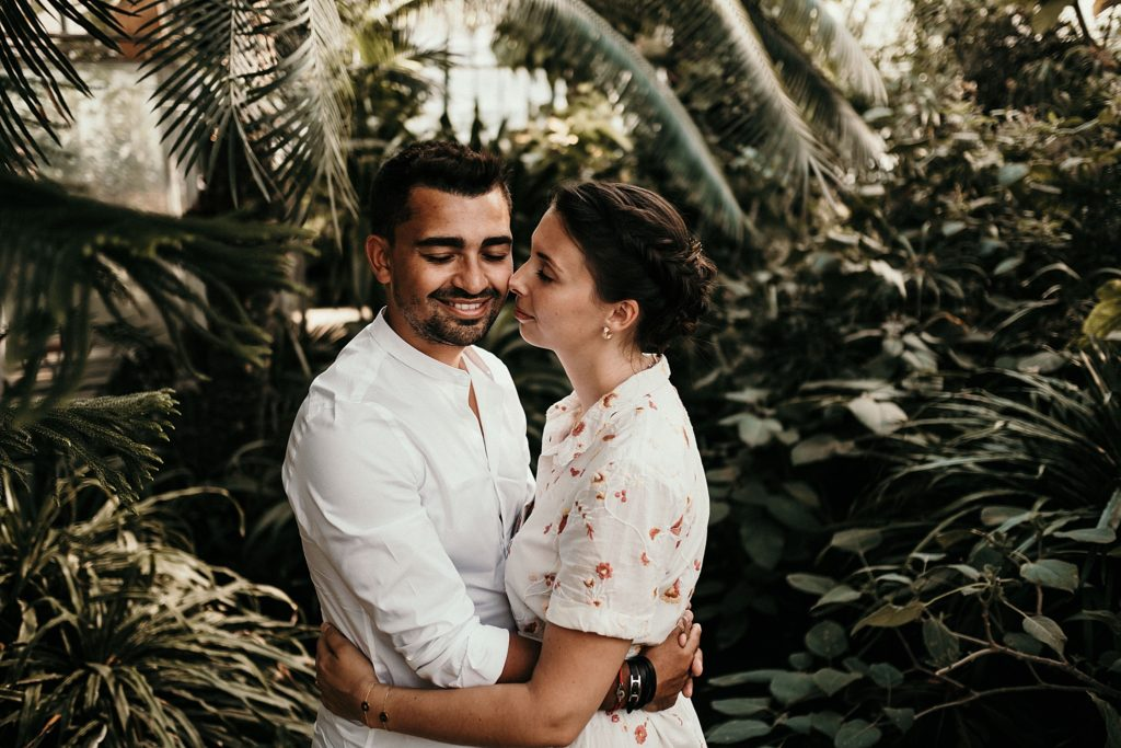 Séance engagement à Paris aux Serres d'Auteuil couple dans serres
