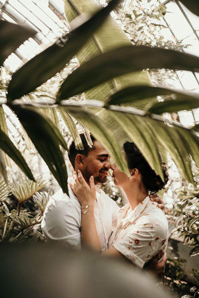Séance engagement à Paris aux Serres d'Auteuil amoureux dans la végétation