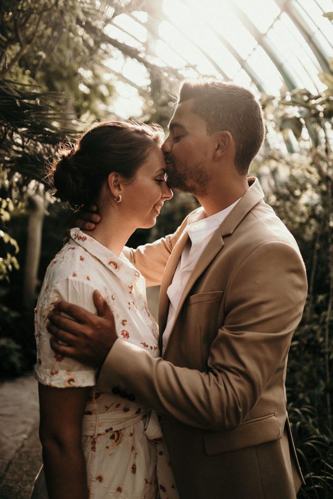 Séance engagement à paris couple qui s'embrasse sous les serres