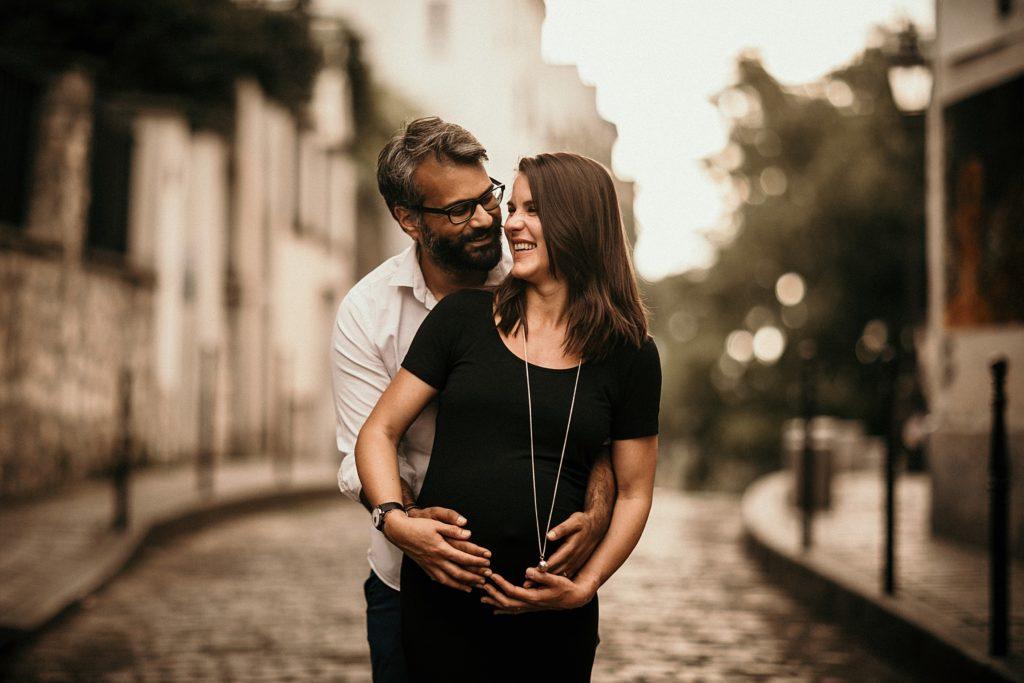 Séance photo grossesse Paris couple sourire soleil montmartre