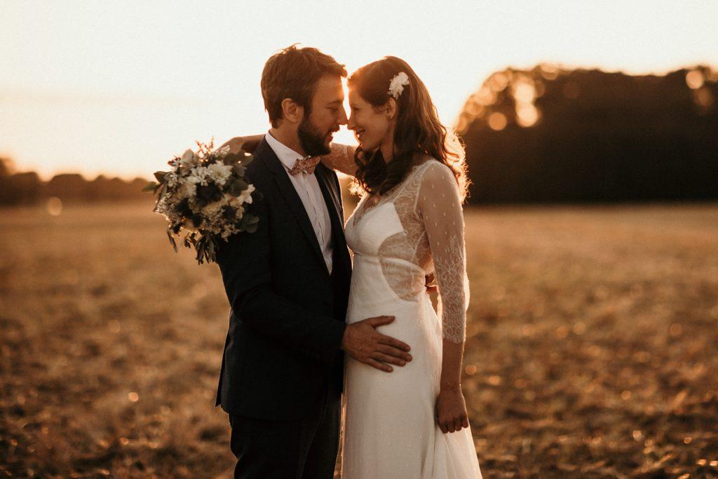 Cérémonie en extérieur photo de couple au coucher de soleil mariage