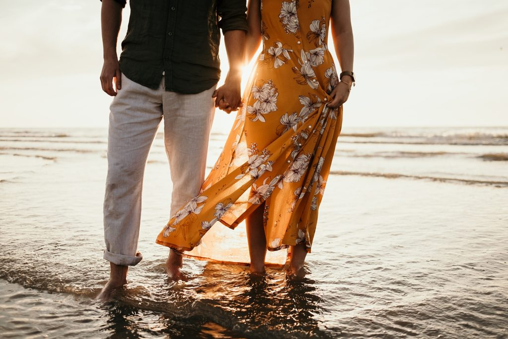Séance photo à la plage les pieds dans l'eau en amoureux